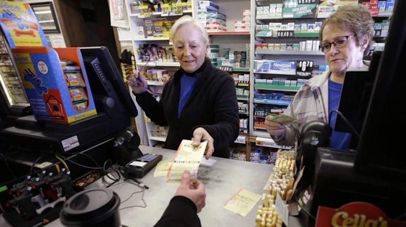 Cashiers sell a lottery ticket at Reeds Ferry Market where the winning ticket was sold. Source: AP
