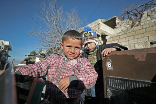 Children stand in the back of a truck as their father, Abu Ismail, prepares to evacuate them from the jihadist-held town of Maaret al-Numan in Syria's Idlib province