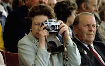 <p>Although she is the most photographed woman in the world, the Queen has been a lifelong fan of photography. Here, she captures a photo with her camera at the Royal Windsor Horse Show in 1982.</p>
