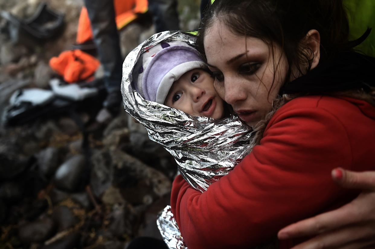 A woman hugs a baby wrapped in an emergency blanket as refugees and migrants arrive on the Greek island of Lesbos after crossing the Aegean sea from Turkey on October 1, 2015.