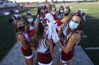 Herriman cheerleaders carry the American flag before the start of a high school football game against Davis, on Thursday, Aug. 13, 2020, in Herriman, Utah. Utah is among the states going forward with high school football this fall despite concerns about the ongoing COVID-19 pandemic that led other states and many college football conferences to postpone games in hopes of instead playing in the spring. (AP Photo/Rick Bowmer)