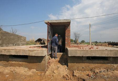 Workers get inside a concrete bunker after its construction in a residential area near the border with Pakistan in Samba sector