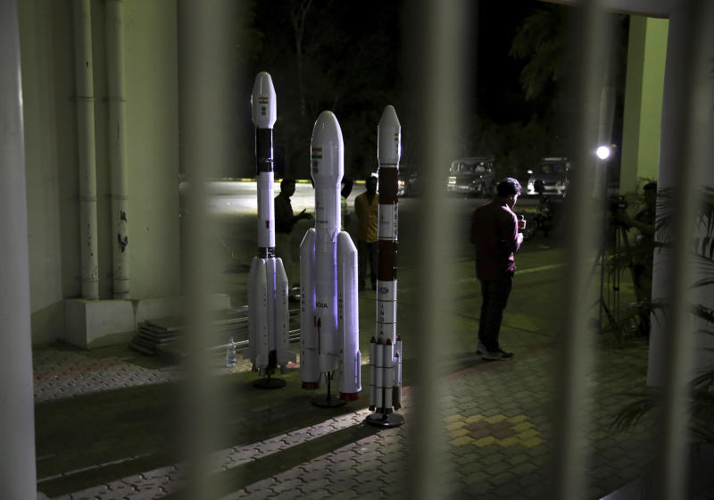 """An Indian Video journalist reports standing next to models of Indian Space Research Organization (ISRO)'s Geosynchronous Satellite launch Vehicle (GSLV) MkIII at Satish Dhawan Space Center after the Chandrayaan-2 mission was aborted at the last minute at Sriharikota, in southern India, Monday, July 15, 2019. India has called off the launch of a moon mission to explore the lunar south pole. The Chandrayaan-2 mission was aborted less than an hour before takeoff on Monday. An Indian Space Research Organization spokesman says a """"technical snag"""" was observed in the 640-ton launch-vehicle system. (AP Photo/Manish Swarup)"""