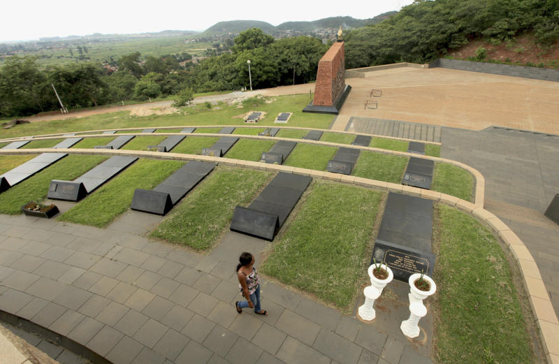 FILE - In this Tuesday Jan. 26, 2016 file photo, a woman walks past rows of graves at the National Heroes Acre in Harare. Robert Mugabe will be buried at the hilltop shrine reserved exclusively for Zimbabwe's ruling elite, an official said Saturday Sept. 7, 2019, as the southern African nation began several days of official mourning. (AP Photo/Tsvangirayi Mukwazhi, File)