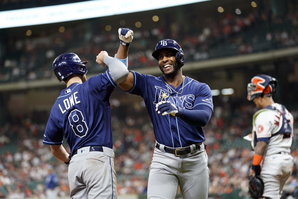 Tampa Bay Rays' Yandy Diaz, right, celebrates with Brandon Lowe (8) after both scored on Diaz's home run against the Houston Astros during the first inning of a baseball game Tuesday, Sept. 28, 2021, in Houston. (AP Photo/David J. Phillip)
