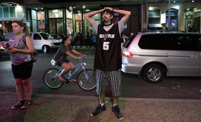 San Antonio Spurs fan Steven Thompson, center, stands outside a restaurant with other fans as they watch the Spurs fall to the Miami Heat in game 7 of the NBA Finals Basketball game, Thursday, June 20, 2013, in San Antonio. Miami won 95-88. (AP Photo/Eric Gay)