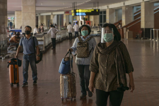 Passengers wear masks and visors at Soekarno-Hatta International Airport in Indonesia. (Getty Images)