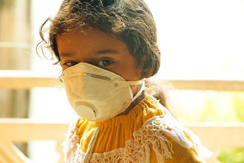 Asian child girl wearning mask to save herself from the environmental air pollution