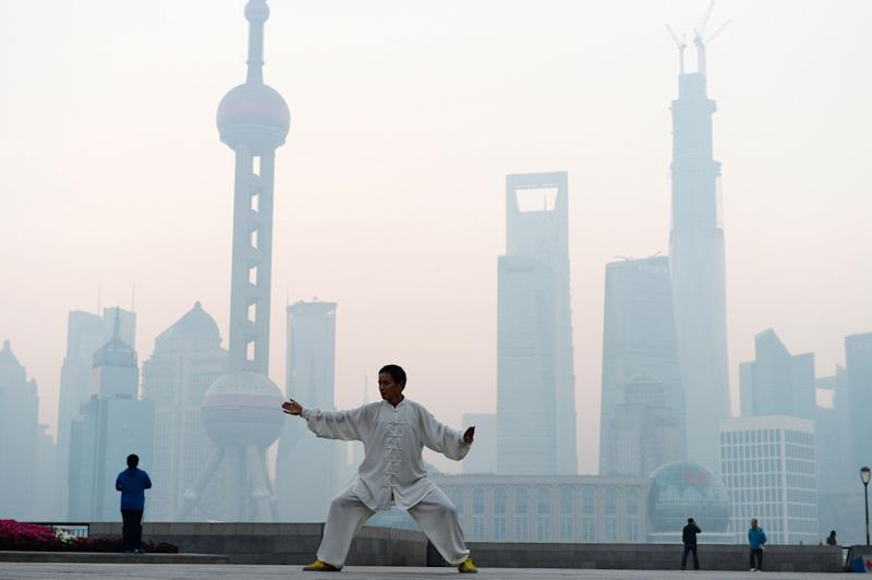 SHANGHAI, CHINA - NOVEMBER 07: (CHINA OUT) A man practices Tai Chi at the Bund as heavy smog engulfs the city on November 7, 2013 in Shanghai, China. People were advised to stay indoors today as the Shanghai Environment Agency measured air pollution levels at five out of a possible six. (Photo by ChinaFotoPress/ChinaFotoPress via Getty Images)