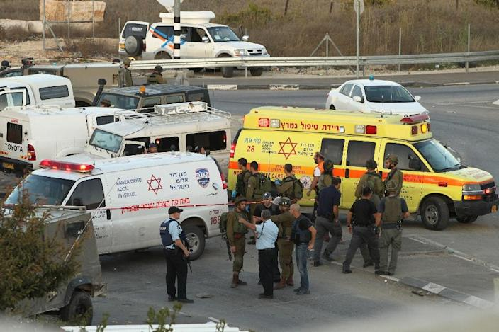 Israeli security forces and emergency personnel gather at the site of a reported car-ramming attack on Israeli border guards at the Beit Einun junction, north of the West Bank city of Hebron, on November 1, 2015 (AFP Photo/Hazem Bader)