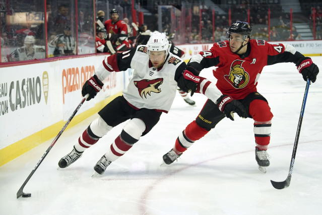 Arizona Coyotes left wing Taylor Hall (91) skates with the puck past Ottawa Senators center Jean-Gabriel Pageau (44) during first-period NHL hockey game action in Ottawa, Ontario, Thursday, Feb. 13, 2020. (Chris Wattie/The Canadian Press via AP)