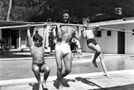 <p>Kirk Douglas uses a pole to lift his sons on the deck of a swimming pool, circa 1955. </p>