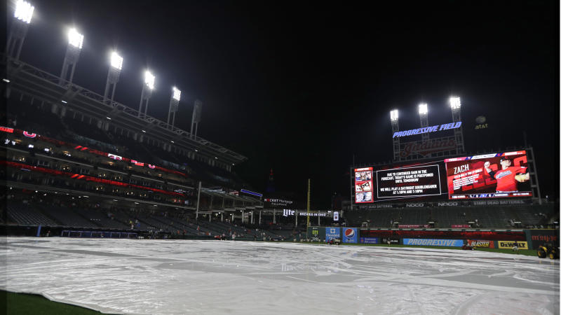 The tarp rests on the field after a baseball game between the Minnesota Twins and the Cleveland Indians is postponed due to the weather, Friday, Sept. 13, 2019, in Cleveland. The Indians and Twins will play a doubleheader on Saturday. (AP Photo/Tony Dejak)