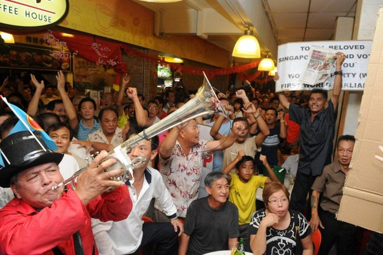 Workers' Party supporters celebrate after the results for the Punggol east by-election was announced.