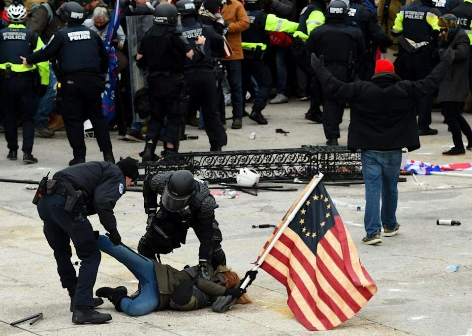Police detain a person as supporters of Donald Trump riot at the US Capitol on 6 January.