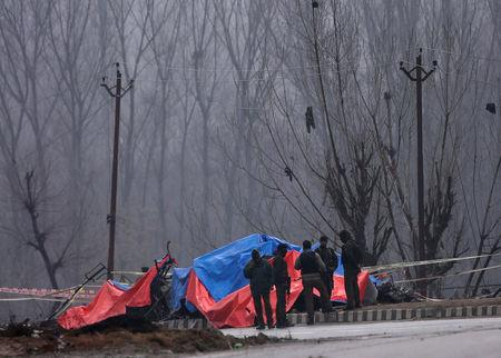 FILE PHOTO: Forensic and security officials stand next to the wreckage of a bus after a suicide bomber rammed a car into the bus carrying Central Reserve Police Force (CRPF) personnel on Thursday, in Lethpora in south Kashmir's Pulwama district, February 15, 2019. REUTERS/Danish Ismail/File Photo