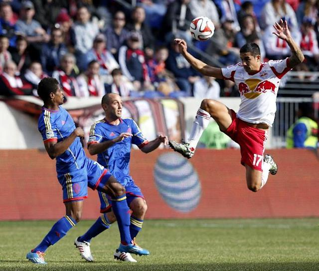 New York Red Bulls midfielder Tim Cahill, right, jumps up while challenging for the ball against Colorado Rapids forward Deshorn Brown, left, and midfielder Nick LaBrocca during the first half of an MLS soccer game, Saturday, March 15, 2014, in Harrison, N.J. (AP Photo/Julio Cortez)