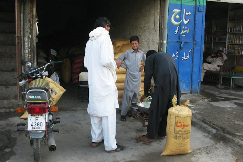 In this Tuesday, Sept. 4, 2012 photo, Pakistani customers from the tribal area of Waziristan buy fertilizer at a shop in Bannu, Pakistan. Pakistan's efforts to cut off the flow of fertilizer to militants using it to make bombs in a key tribal sanctuary along the Afghan border has outraged local farmers, who complain the policy has failed to stymie insurgents but has cut their crop yields in half. (AP Photo/Ijaz Muhammad)