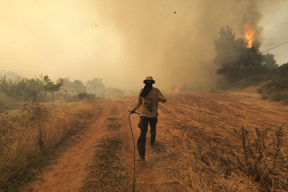 A man runs as fire burns trees in Kirinthos village on the island of Evia, about 135 kilometers (84 miles) north of Athens, Greece, Friday, Aug. 6, 2021. Thousands of people fled wildfires burning out of control in Greece and Turkey on Friday, including a major blaze just north of the Greek capital of Athens that claimed one life, as a protracted heat wave left forests tinder-dry and flames threatened populated areas and electricity installations. (AP Photo/Thodoris Nikolaou)
