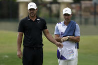Brooks Koepka looks over a putt with his caddie, Ricky Elliott on the 16th hole during the second round of the World Golf Championship-FedEx St. Jude Invitational Friday, July 31, 2020, in Memphis, Tenn. (AP Photo/Mark Humphrey)
