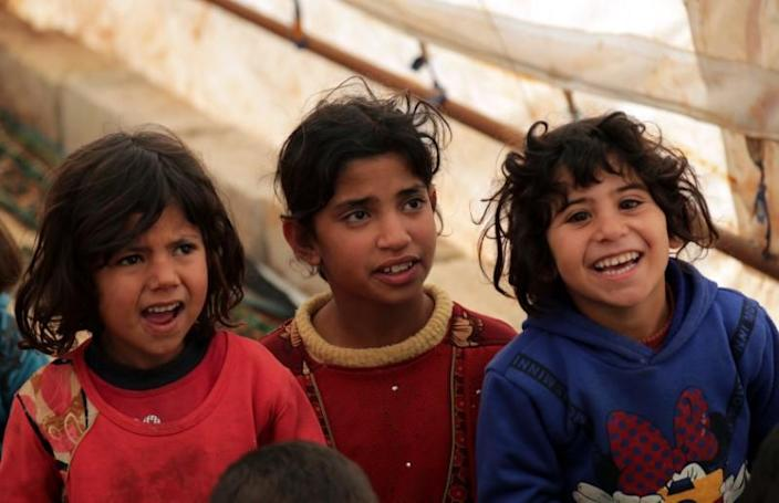 Students sit together at a makeshift school in a tent in Azaz