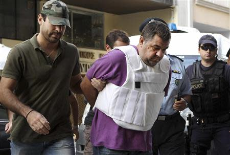Police officers escort a man (C), a supporter of the far-right Golden Dawn group and who admitted to the fatal stabbing of anti-racism rapper Pavlos Fissas, into a prosecutor's office in Piraeus, near Athens September 21, 2013. REUTERS/John Kolesidis