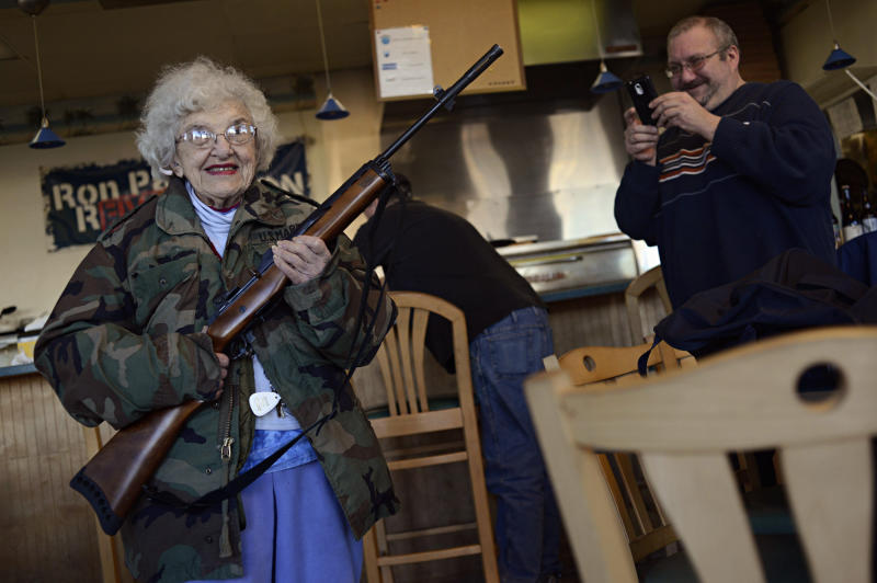 Lee Lazernick, right, asked his mother Thelma Lazernick, left, to pose with a customer's Ruger Mini-14 .223 semi-automatic rifle on Monday, Feb. 18, 2013, at All Around Pizza and Deli in Virginia Beach, Va., where customers wearing weapons or who bring their concealed weapons permit are offered a 15 percent discount. (AP Photo/The Virginian-Pilot, Amanda Lucier) MAGS OUT