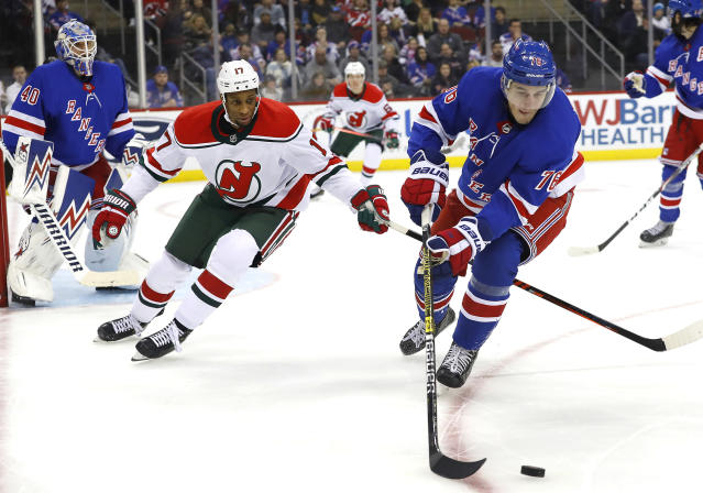 New York Rangers defenseman Brady Skjei (76) plays the puck against New Jersey Devils right wing Wayne Simmonds during the second period of an NHL hockey game Saturday, Nov. 30, 2019, in Newark, N.J. (AP Photo/Noah K. Murray)