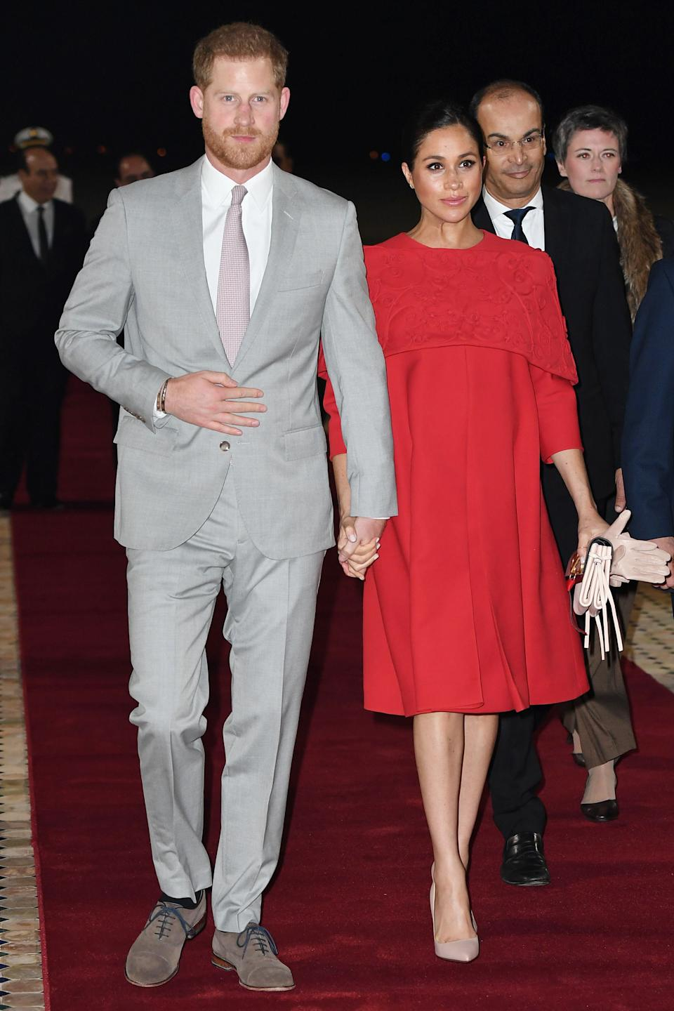 Demonstrating how to fly the sartorial flag while on tour, the Duchess of Sussex chose a red caped Valentino gown for her arrival into Morocco. <em>[Photo: Getty]</em>