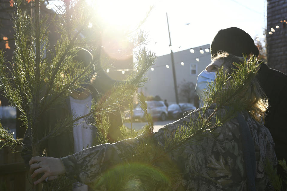 Parker Vivier (R), of Richmond, looks at a tree to buy at Frank Pichel's tree lot, Sunday, Dec. 6, 2020, in Richmond, Va. A Virginia man has found a way to use Charlie Brown-style Christmas trees to benefit a middle school that provides scholarships for students from an impoverished area. (AP Photo/Will Newton)