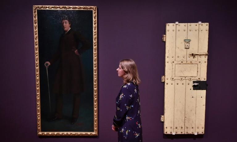 "Oscar Wilde's prison door (right) and an oil painting entitled ""Oscar Wilde"" by US artist Robert Harper are part of the ""Queer British Art 1861-1967"" exhibition at the Tate Britain in London"