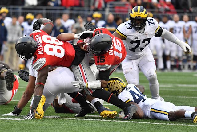 "COLUMBUS, OH – NOVEMBER 26: <a class=""link rapid-noclick-resp"" href=""/ncaaf/players/225823/"" data-ylk=""slk:J.T. Barrett"">J.T. Barrett</a> #16 of the <a class=""link rapid-noclick-resp"" href=""/ncaab/teams/oad/"" data-ylk=""slk:Ohio State Buckeyes"">Ohio State Buckeyes</a> rushes for a first down during overtime of the game against the <a class=""link rapid-noclick-resp"" href=""/ncaab/teams/max/"" data-ylk=""slk:Michigan Wolverines"">Michigan Wolverines</a> at Ohio Stadium on November 26, 2016 in Columbus, Ohio. (Photo by Jamie Sabau/Getty Images)"