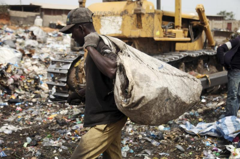 A scavenger picks up trash for recycling at the Olusosun dump site in Nigeria's commercial capital Lagos in this March 23, 2012 file photo. One thing Nigeria's megacity of Lagos, one of the world's largest, generates in abundance is trash. Now it plans to turn that rubbish into electricity which the city desperately lacks. Ola Oresanya, managing director of the Lagos Waste Management Authority (LAWMA) aims to complete the project in around five years, by which time it will have a 25 megawatt (mw) capacity, he said. That is only 1 percent of the 2,000 - 3,000 mw that he estimates Lagosians demand, but it is a start. To match story NIGERIA-RUBBISH/ELECTRICITY/ REUTERS/Akintunde Akinleye/Files (NIGERIA - Tags: ENERGY SOCIETY ENVIRONMENT)