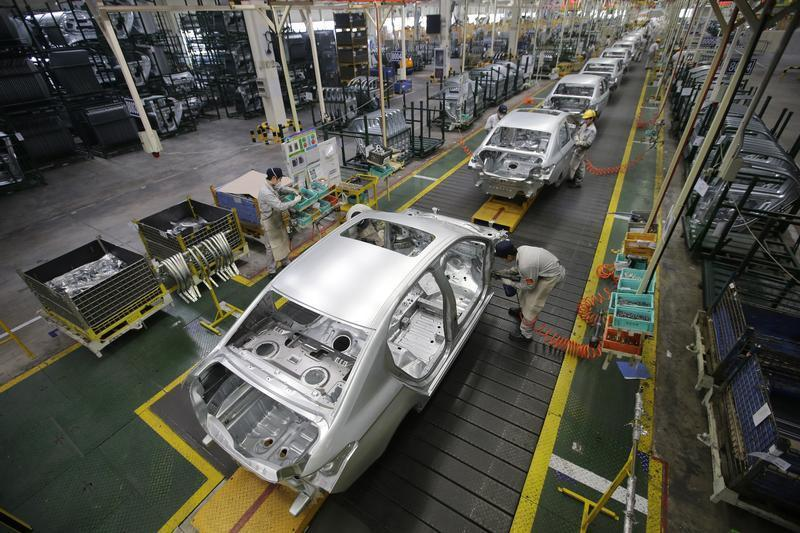 Employees assemble cars at a production line of Dongfeng Peugeot Citroen Automobile factory in Wuhan