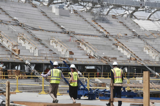 Members of the media take a tour of the new NFL Los Angeles Stadium while under construction during a topping-out ceremony in Inglewood, Calif. on Monday April 15, 2019. Stadium officials hosted a tour for the media after the final piece of the canopy structure to hold the roof was completed. (AP Photo/Richard Vogel)