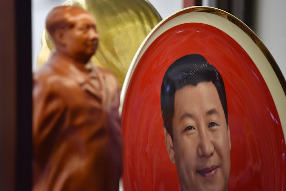 <p>A decorative plate featuring an image of Chinese President Xi Jinping is seen behind a statue of late communist leader Mao Zedong at a souvenir store next to Tiananmen Square in Beijing on 27 February, 2018</p> (GREG BAKER/AFP via Getty Images)