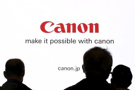 FILE PHOTO - People are silhouetted against a display of the Canon brand logo at CP+ camera and photo trade fair in Yokohama