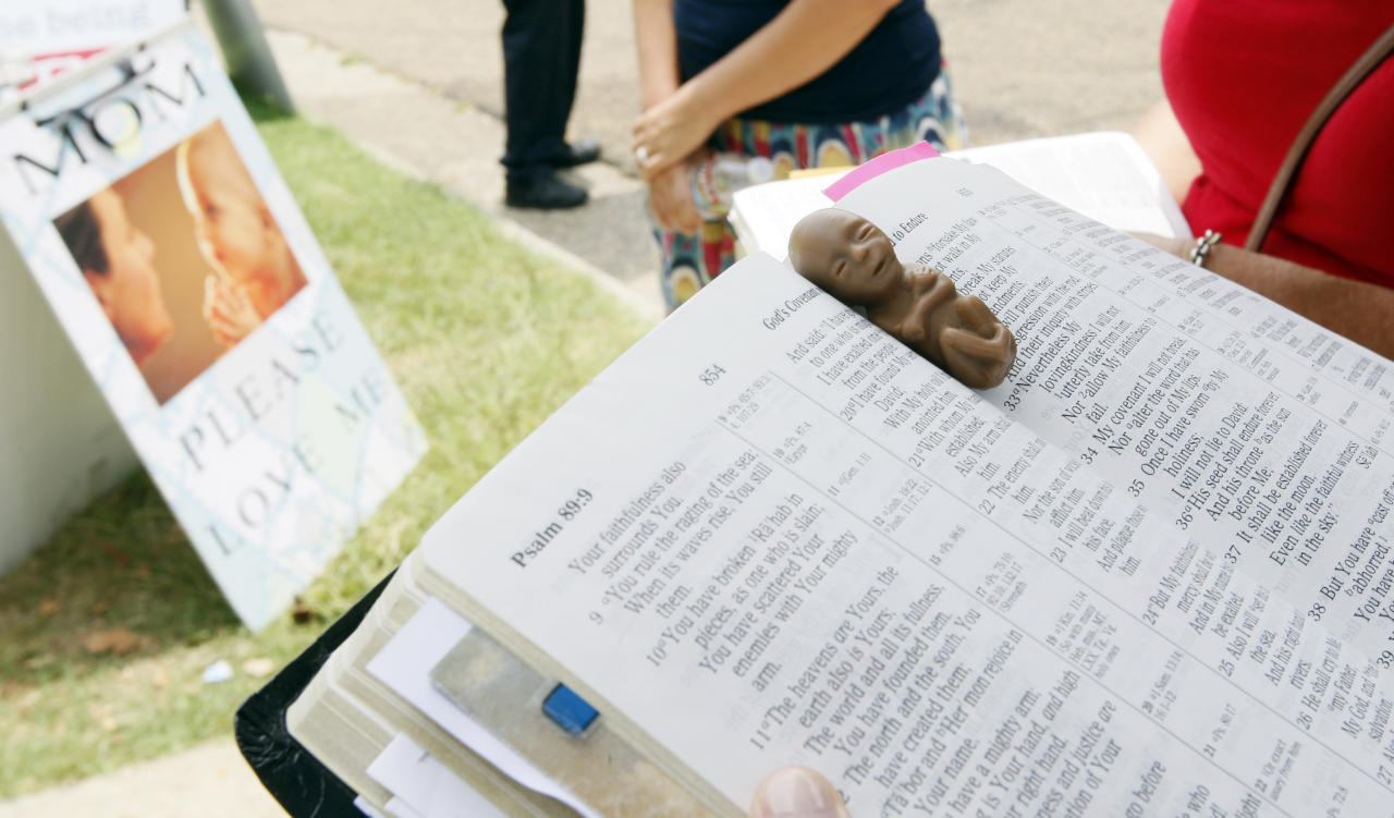 Abortion opponents pray outside Mississippi's only abortion clinic in Jackson, Miss., Monday, July 2, 2012, after a federal judge issued a temporary restraining order Sunday, that blocked enforcement of a law that could regulate it out of business. On the Bible is a plastic 12-week old fetus. (AP Photo/Rogelio V. Solis)