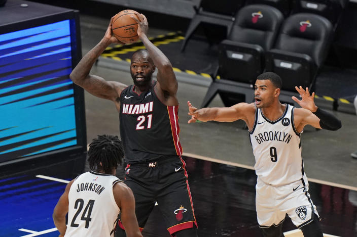 Miami Heat center Dewayne Dedmon (21) passes the ball past Brooklyn Nets forward Alize Johnson (24) and guard Timothe Luwawu-Cabarrot (9) during the first half of an NBA basketball game, Sunday, April 18, 2021, in Miami. (AP Photo/Wilfredo Lee)