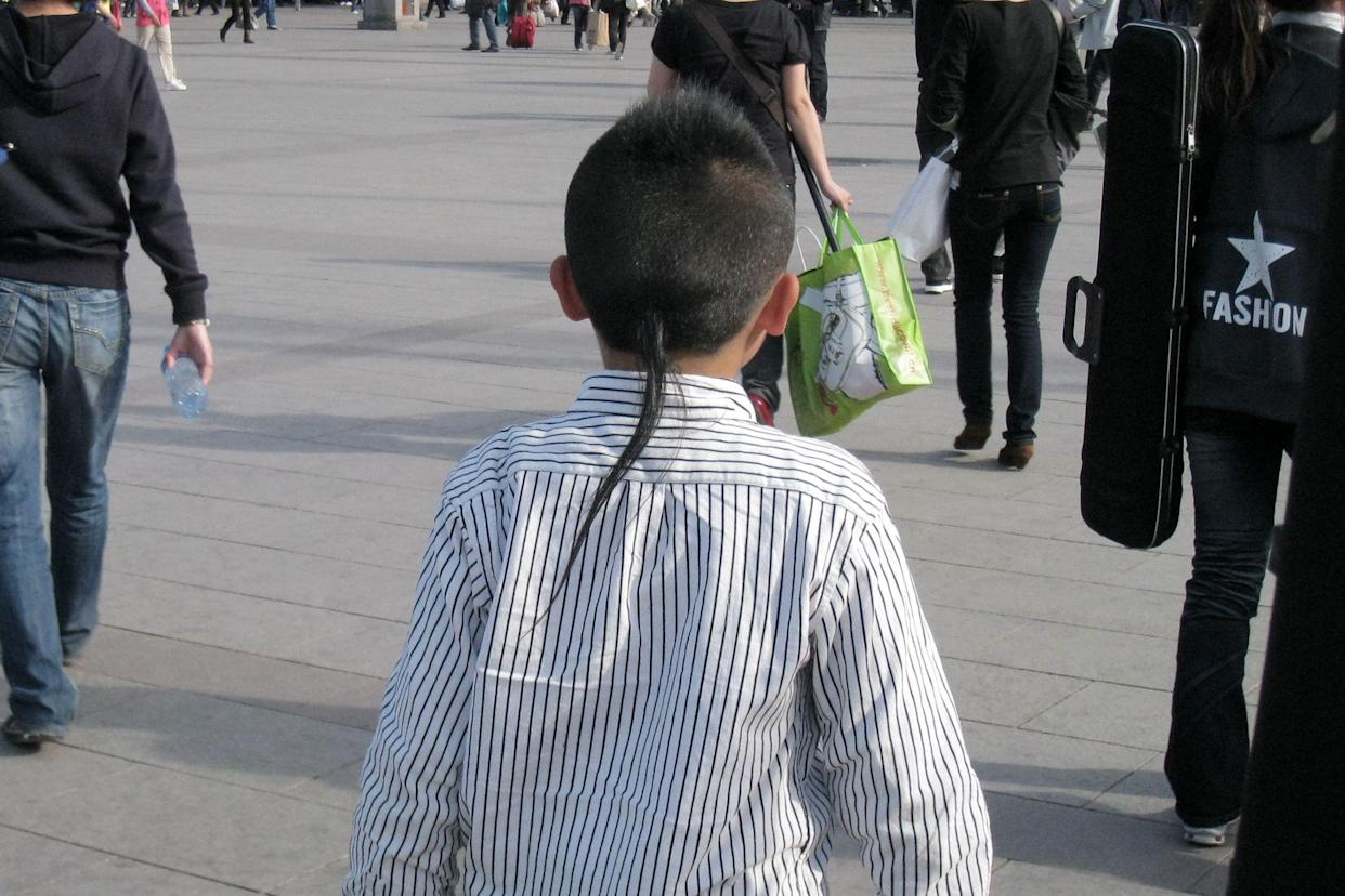 Back of a young boy's head with a rat tail haircut