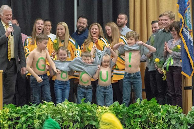 Clarkson University president Anthony G. Collins, left, acknowledged the Lil' Knights as the women's hockey team's biggest fans at a recent national championship ceremony. (Provided by Shannon Desrosiers)