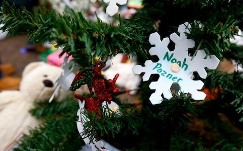 A snowflake ornament hangs on a Christmas tree at a makeshift memorial in Newtown - Credit: Julio Cortez/AP