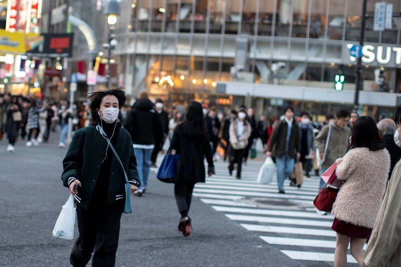 A woman wearing a protective face mask runs across a street at Shibuya in Tokyo