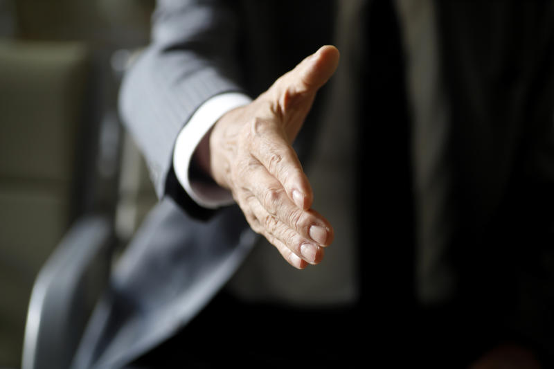 A photo of a man wearing a suit extending their hand for a handshake, which Brendan Murphy says people won't be able to engage in for a while.