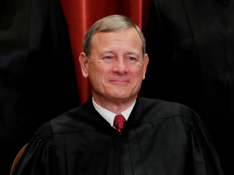 U.S. Supreme Court Chief Justice John Roberts poses during group portrait at the Supreme Court in Washington