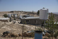 A new water tank rests on a stand after it replaced a damaged one following a settlers' attack from nearby settlement outposts on the Palestinian Bedouin community, in the West Bank village of al-Mufagara, near Hebron, Thursday, Sept. 30, 2021. Residents of a small Palestinian shepherding village in the occupied West Bank say an Israeli settler attack last week was one of the most violent episodes of a series of recent incidents. (AP Photo/Nasser Nasser)