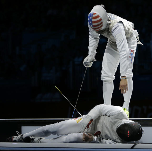 Sebastian Bachman of Germany lies injured after falling off of the center piste while competing against Gerek Meinhardt of the United States, right, during the men's foil team fencing competition at the 2012 Summer Olympics, Sunday, Aug. 5, 2012, in London. (AP Photo/Dmitry Lovetsky)