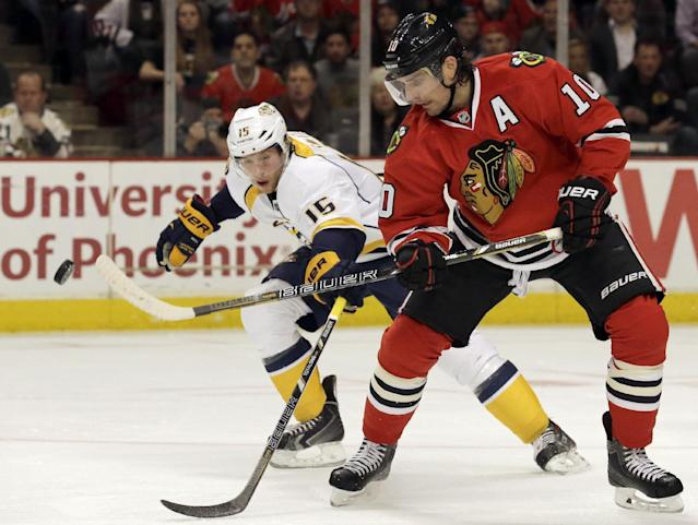 Chicago Blackhawks' Patrick Sharp (10) controls the puck against Nashville Predators' Craig Smith (15) during the first period of an NHL hockey game in Chicago, Friday, March 14, 2014. (AP Photo/Nam Y. Huh)