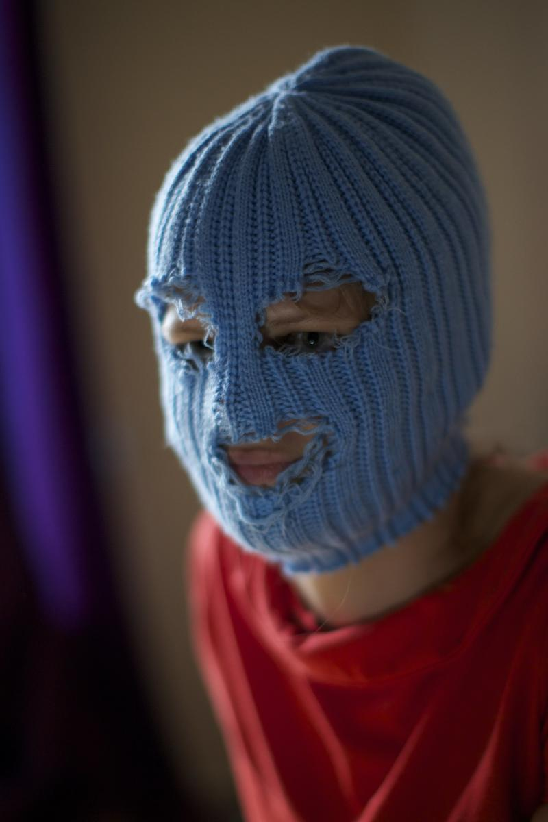 """A member of Russian punk band Pussy Riot, who gave only her stage name of Grelka, wears a blue balaclava as speaks to the media in Moscow, Tuesday, July 16, 2013. Russian provocateurs Pussy Riot are back in action, releasing their first music video since three members went to prison last year for a prank denouncing Vladimir Putin. The video shows band members in trademark bright-colored balaclavas and short skirts, cavorting and shrieking atop an oil rig. Backed by hectic guitar and a drum fusillade, they pour oil on a large photo of state oil giant Rosneft's chairman and liken Putin to an Iranian ayatollah. Pussy Riot member Grelka said after the video's Tuesday release that """"the main message is that Putin has spread the country's wealth among his friends."""" (AP Photo/Alexander Zemlianichenko)"""