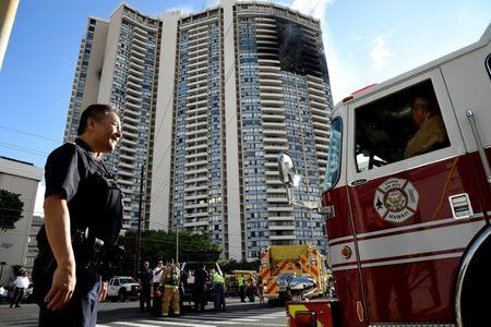 A police officer directs a fire truck at the Marco Polo apartment building after a fire broke out in it in Honolulu, Hawaii, July 14, 2017.  REUTERS/Hugh Gentry